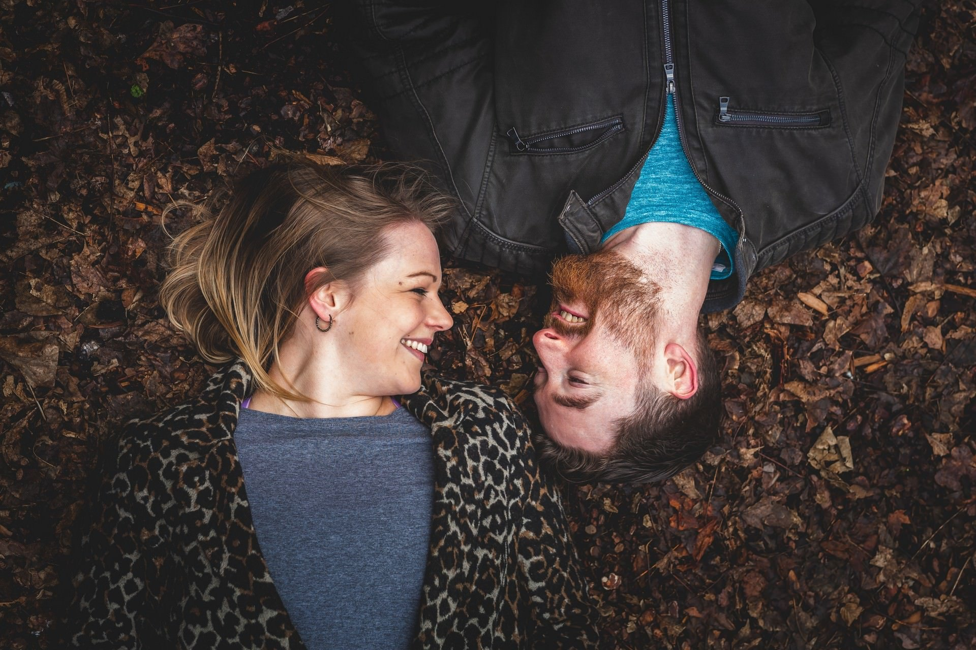 Couple lying down in the autumn leaves looking at each other