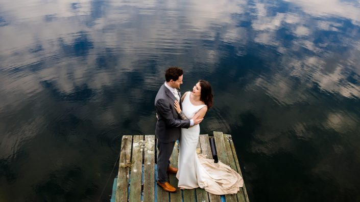 Bride and groom standing on jetty floating on lake with reflection of clouds.